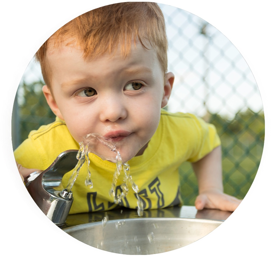 Boy drinking water from water fountain